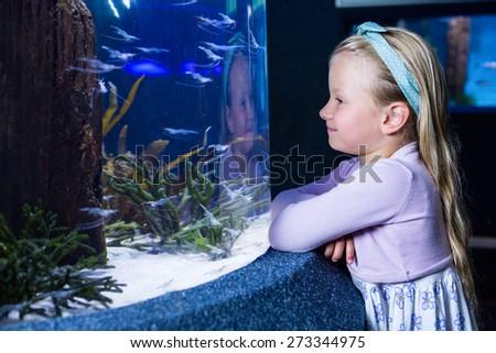 Happy young woman looking at fish in a tank at the aquarium - stock photo