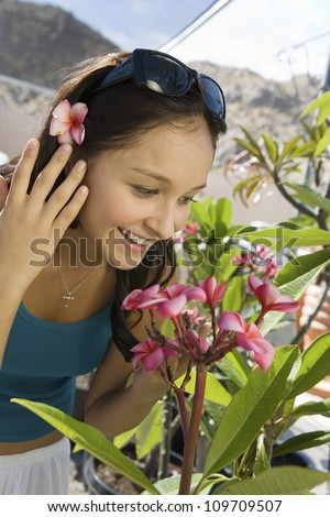 Happy young woman looking at flowers at botanical garden
