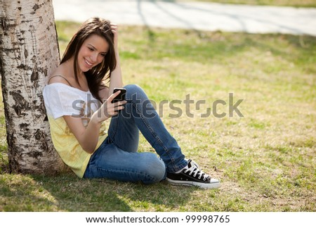 happy young woman looking at her phone - stock photo