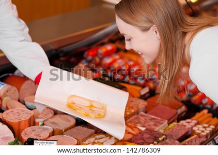 Happy young woman looking at sliced meat on butcher hand at supermarket - stock photo