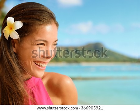 Happy young woman looking away at beach. Attractive female is with frangipani flower in her hair. Beautiful tourist is enjoying her vacation. - stock photo