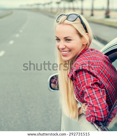 Happy young woman looking out from car window  - stock photo