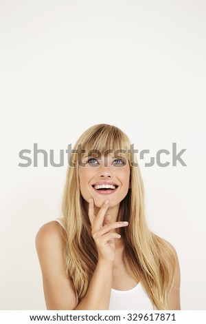 Happy young woman looking up in white studio - stock photo