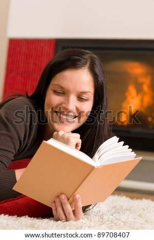 Happy young woman lying by fireplace on carpet reading book - stock photo