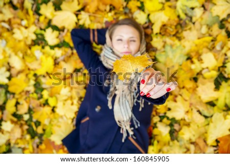Happy young woman lying down resting and dreaming in autumn leaves. Top view