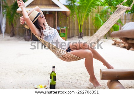 Happy young woman lying in hammock on tropical beach - stock photo
