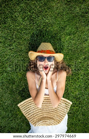 Happy young woman lying on green grass and dreaming. copy space, view from above - stock photo