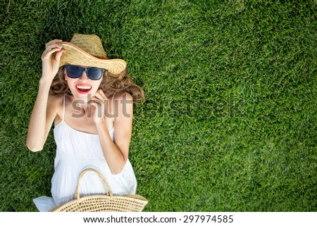 Happy young woman lying on green grass and dreaming. copy space, view from above, soft - stock photo