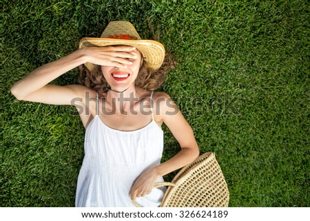 Happy young woman lying on green grass and dreaming. copy space, view from above, soft, focus on hand - stock photo