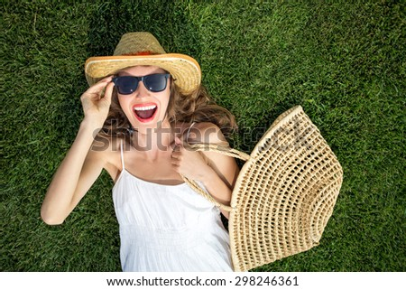 Happy young woman lying on green grass laughing with excitement. copy space, view from above, focus on face and hand with bag - stock photo