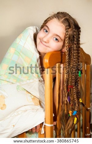 Happy young woman lying on the bed  - stock photo