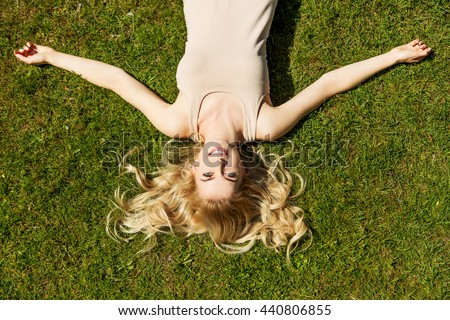 Happy young woman lying on the grass - stock photo