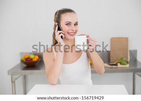Happy young woman making a phone call and holding a mug looking at camera in the kitchen at home - stock photo