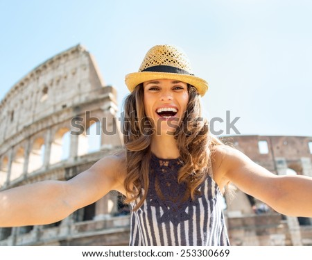 Happy young woman making selfie in front of colosseum in rome, italy - stock photo