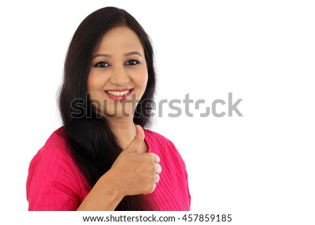 Happy young woman making thumbs up gesture against white background
