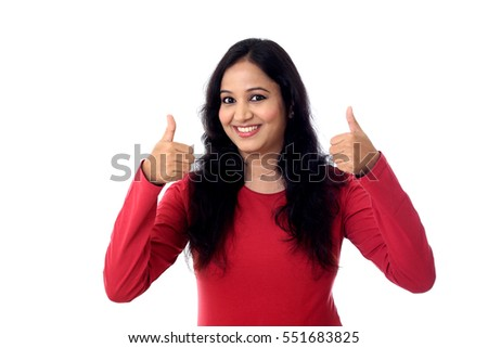 Happy young woman making thumbs up sign against white