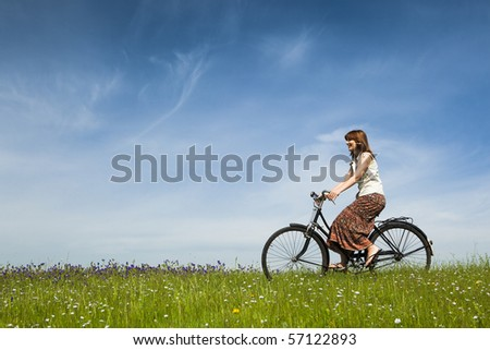 Happy young woman on a green meadow riding a bicycle - stock photo
