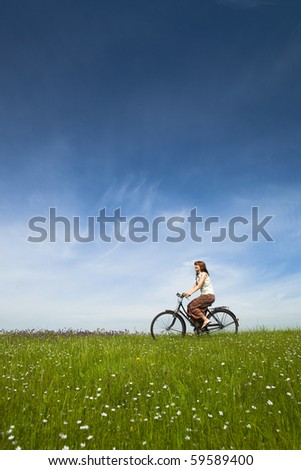 Happy young woman on a green meadow riding a bicycle