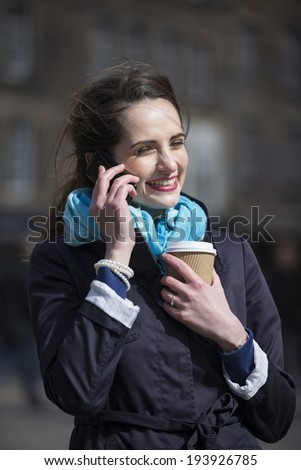 Happy young woman on cell phone outside in City. Beautiful caucasian woman holding coffee cup and using smartphone. - stock photo
