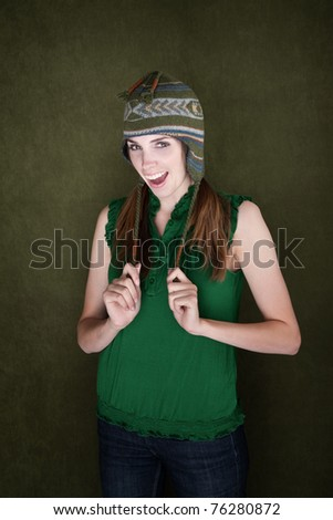 Happy Young Woman on green background with Knit Cap - stock photo