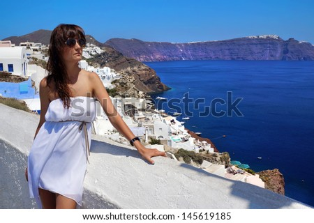 Happy young woman on holidays, Santorini - Fira (Thira)  town view - stock photo