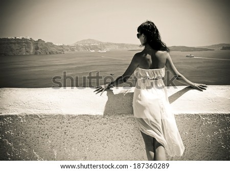 Happy young woman on holidays, Santorini Thira town. Photo in vintage style  - stock photo