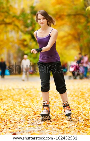 happy young woman on roller skates in the autumn park - stock photo