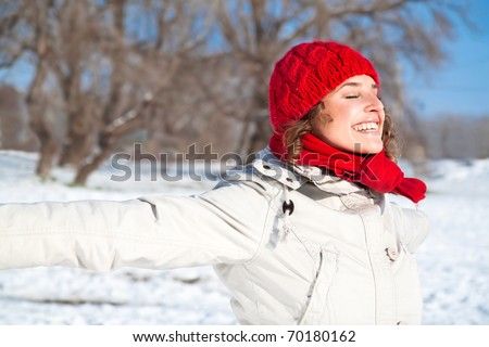 Happy young woman on the snow sunny day against blue sky - stock photo