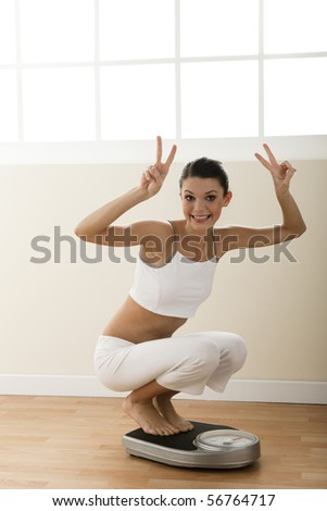 Happy young woman on weight scale - stock photo