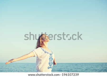 happy young woman open her arms to the sky and sea and enjoying life - stock photo