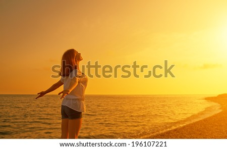happy young woman open her arms to the sky and sea at sunset  and enjoying life - stock photo
