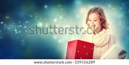 Happy young woman opening a Christmas present box - stock photo