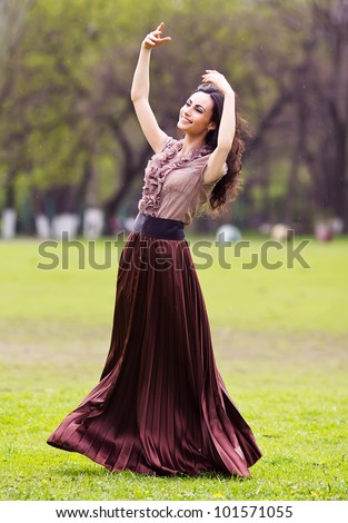 happy young woman outdoors in the field,dancing under the rain - stock photo