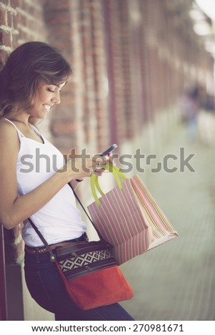 Happy young woman outdoors with mobile phone and shopping bag - stock photo