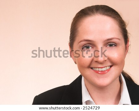 Happy young woman over light beige background smiling with copyspace beside - stock photo