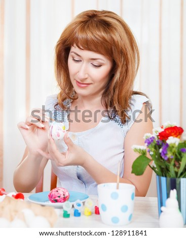 Happy young woman painting Easter eggs