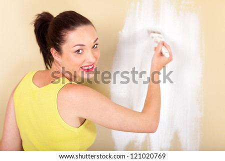 happy young woman painting the wall - stock photo