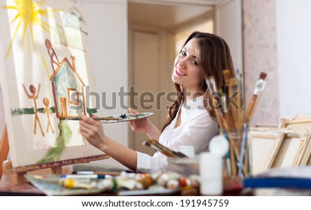 Happy young woman paints home of dreams on canvas in workshop - stock photo