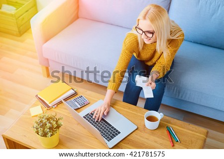 Happy  young woman paying bills on laptop sitting on sofa
