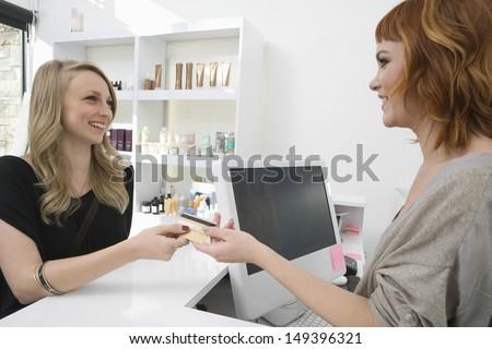 Happy young woman paying through credit card at hair salon - stock photo