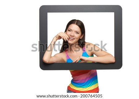 Happy young woman peeping out of tablet frame, over white background - stock photo