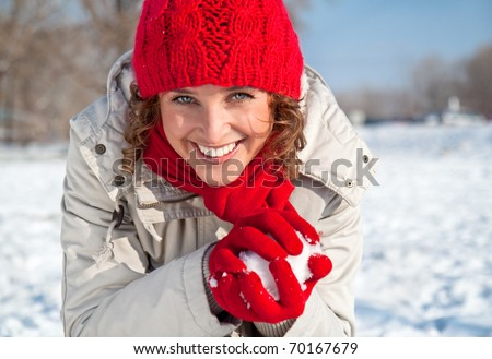 Happy young woman playing snowball fight on the snow sunny day - stock photo