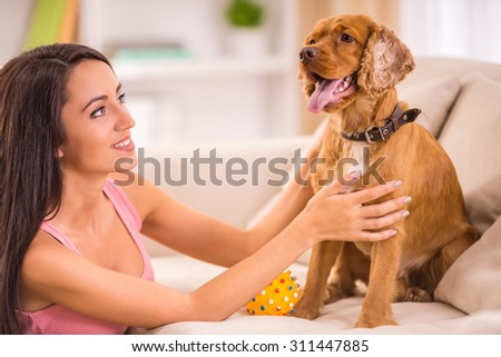 Happy young woman playing with dog at home.