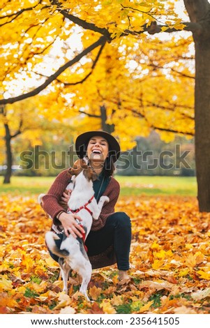 Happy young woman playing with dog outdoors in autumn - stock photo