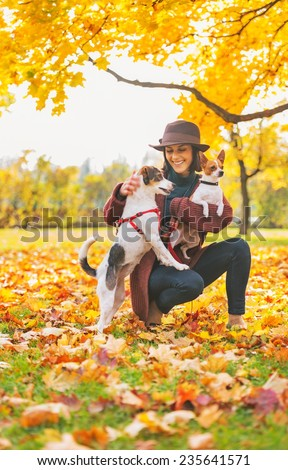 Happy young woman playing with dogs outdoors in autumn - stock photo