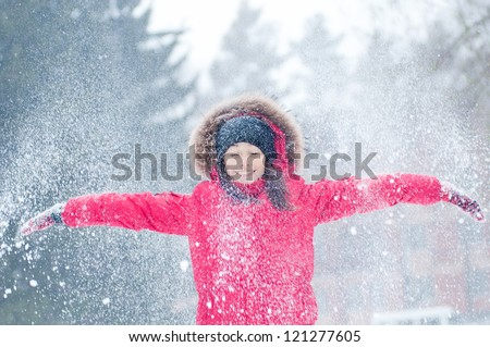Happy young woman plays with a snow outdoor. Winter day