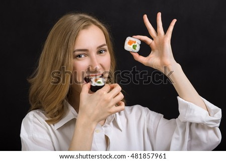 happy young woman plays with sushi looking at camera