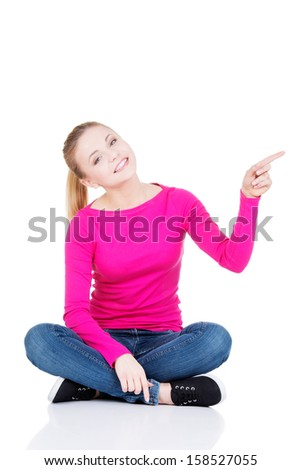 Happy young woman pointing on copy space. Isolated on white - stock photo