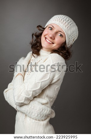 Happy young woman posing in a studio wearing in a sweater and mittens on gray background