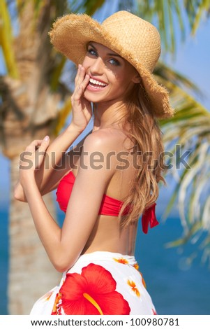 Happy young woman posing in straw hat at exotic surrounding - stock photo